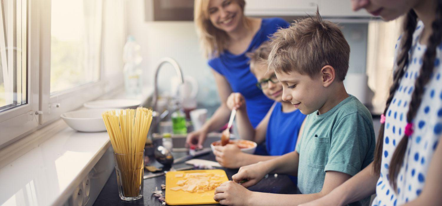 Kids cooking noodles with mum