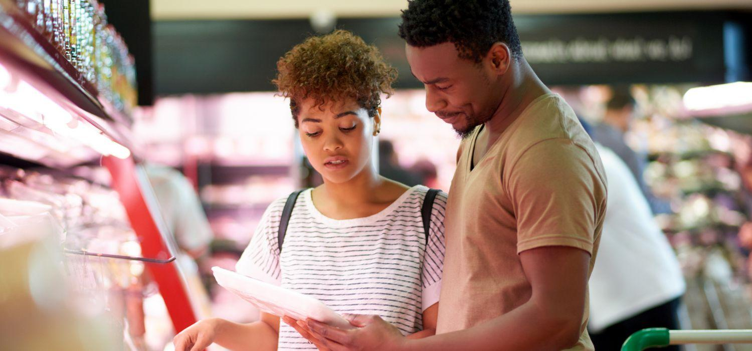 lady and man looking at shopping list in supermarket