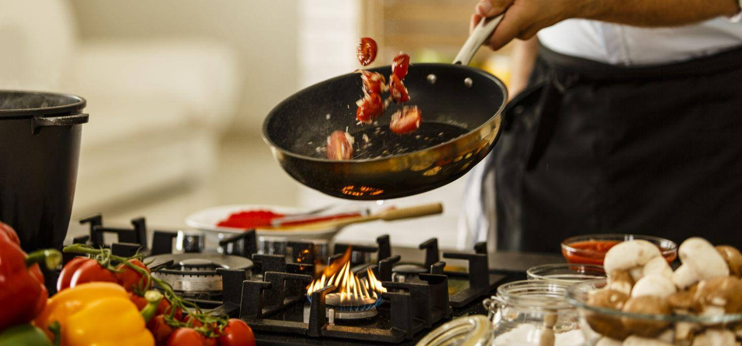 cooking at home and tossing food in frying pan