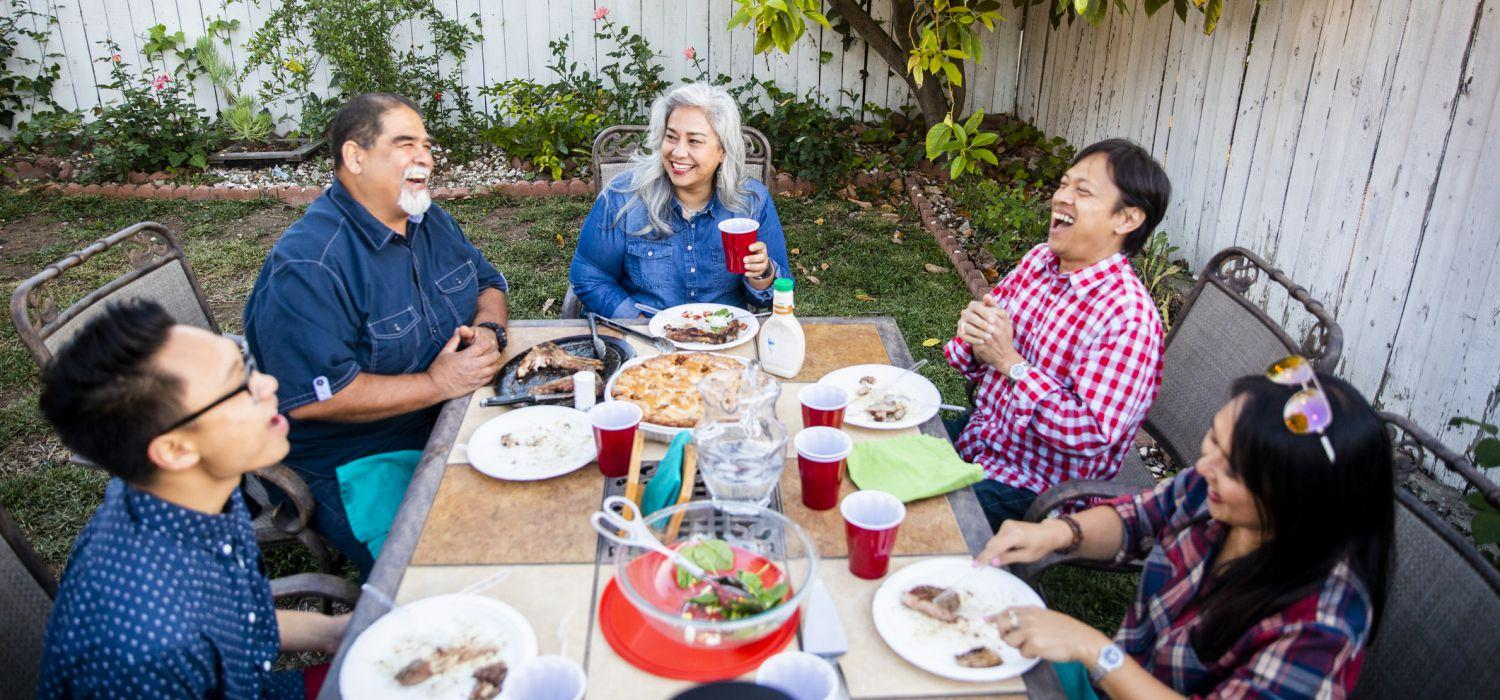 group of people eat in the backyard laughing